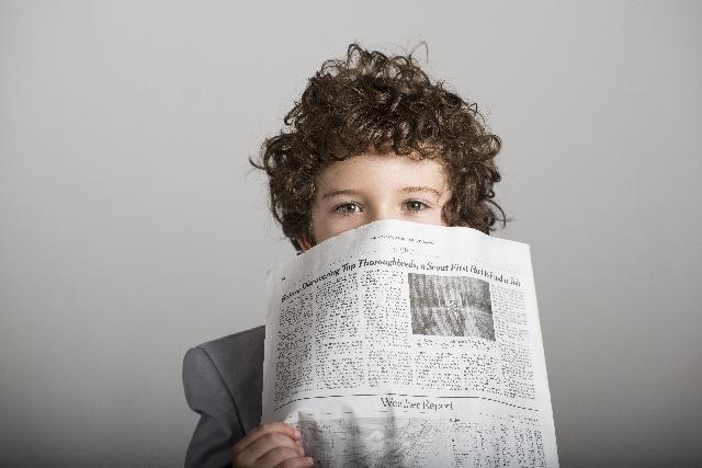 新聞紙をもつ少年